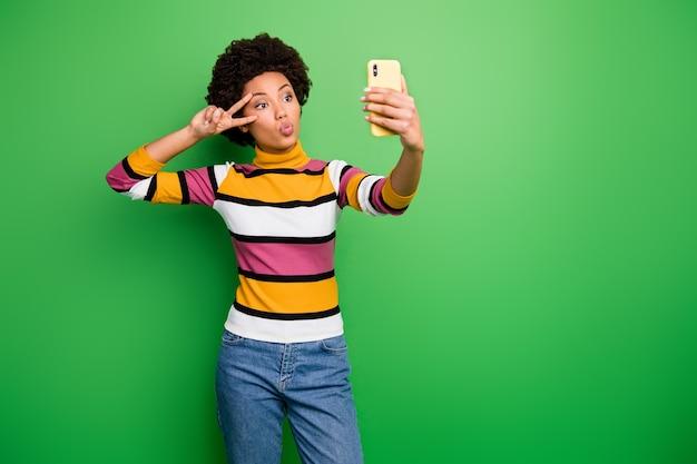 Красивой темнокожей дамы с телефоном, делающей селфи в блоге, показывающим v-образный знак, отправляющим воздушный поцелуй, повседневные полосатые джинсы-пуловеры