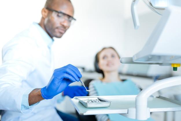 최고의 품질. 초점은 쟁반에 입 거울을 두는 즐거운 젊은 남성 치과 의사의 손에있는
