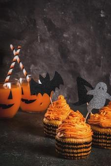 ハロウィーンの面白い子供の御of走の簡単なアイデア:休日のシンボル-幽霊、魔女、コウモリの形の装飾とクリームとカボチャのケーキ。黒のcopyspace