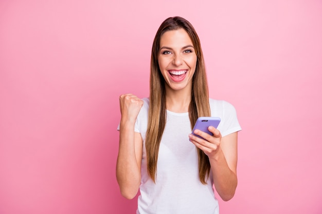 Смешной дамы держите телефон за руки проверьте новые подписчики блога в социальных сетях репосты любит праздновать большие числа носить повседневную белую футболку