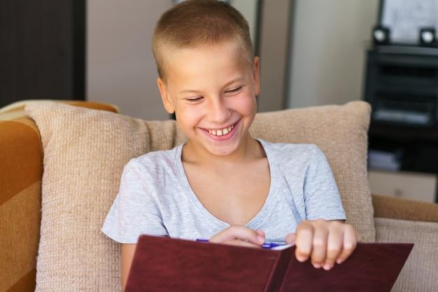 숙제를 하 고 소파에 앉아 모범생의 행복 한 아이 소년 쓰기 펜을 들고