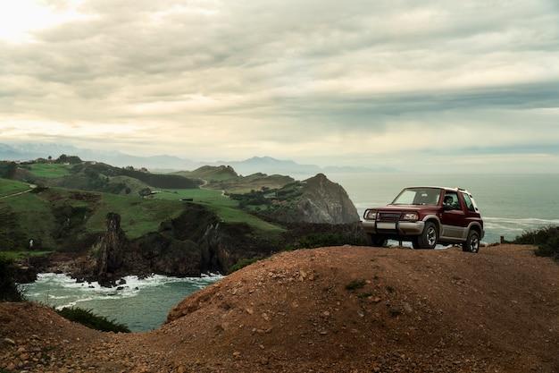 극적인 하늘과 아름다운 해안 풍경과 언덕 꼭대기에 오프로드 자동차