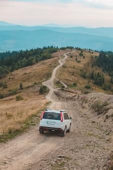 山のピークの秋のシーズンのロードトリップによるオフロード車の旅