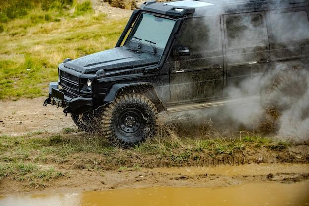 Внедорожная экспедиция на джипах по деревням по горной дороге на классическом автомобиле x пересекает воду с брызгами ...