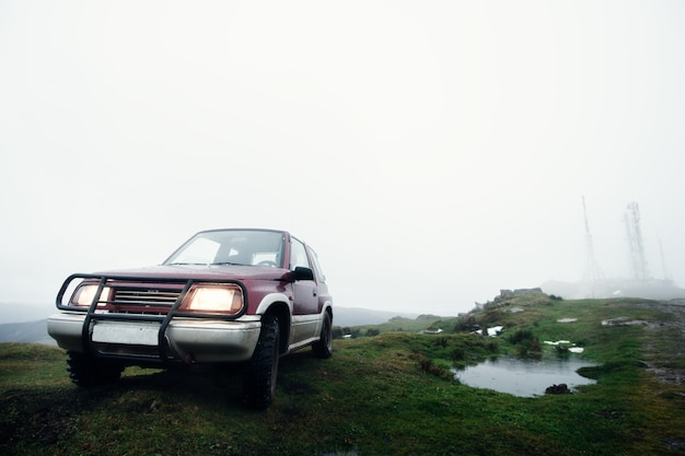 早朝の霧の山のオフロード車