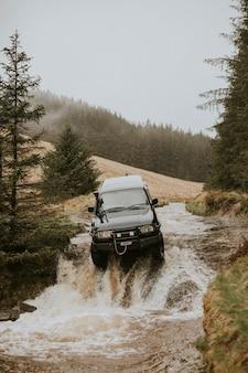 自然の中で水流に引っかかっているオフロード車