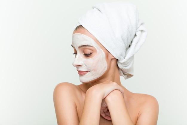 Молодая кавказская женщина наслаждаясь обработкой маски offacial