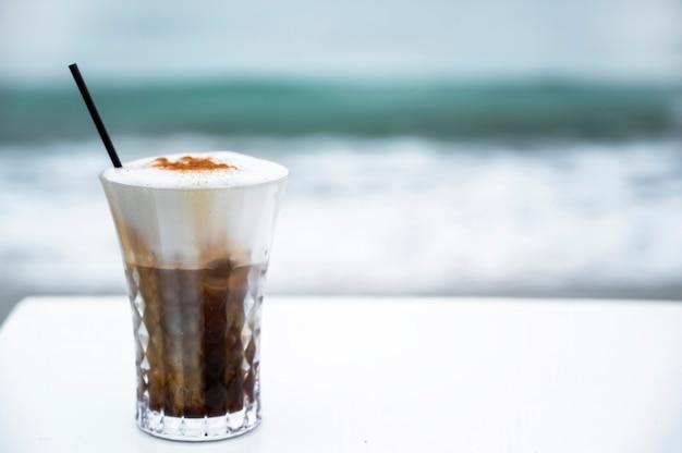 ?海のある白いテーブルの上で泡とストローで飲み物を飲む