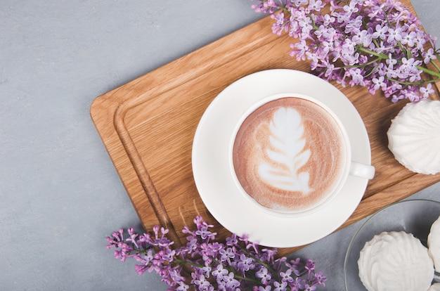 Кофе с латте-арт на сером деревянном столе. плоская планировка