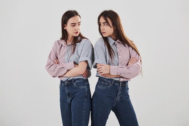Обиделись и посмотри на других с гневом. две сестры-близнецы стоят и позируют