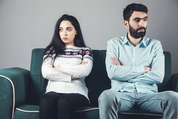 Обиженная и грустная пара, сидящая на диване