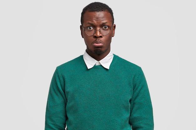 Hipster maschio nero offeso ha uno sguardo pietoso, labbra imbronciate, indossa occhiali rotondi, maglione elegante