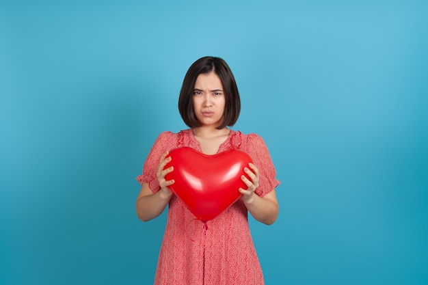 Offended by a bad gift, a young asian woman holds a red heart-shaped balloon in her hands