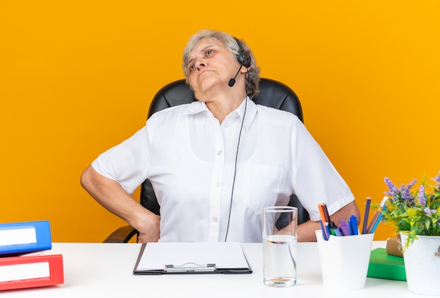Offended caucasian female call center operator on headphones sitting at desk with office tools looking at side