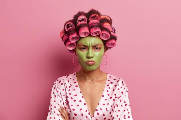 불쾌한 불쾌한 젊은 여성은 미용 제품 효과를 기다리는 데 지친 아름다움 녹색 얼굴 마스크를 적용하고 머리카락에 curlers를 착용하고 장미 빛에 대해 포즈를 취합니다. 주부는 헤어 스타일을 만듭니다.