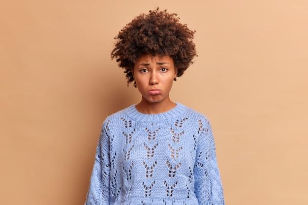 ベージュの壁に隔離された青いジャンパーに身を包んだ不満を持った女性が下唇を前に失望しているように見える不満を持った女性はやっかいな表情をしています