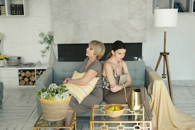 Offended elderly mother and daughter sitting on the sofa
