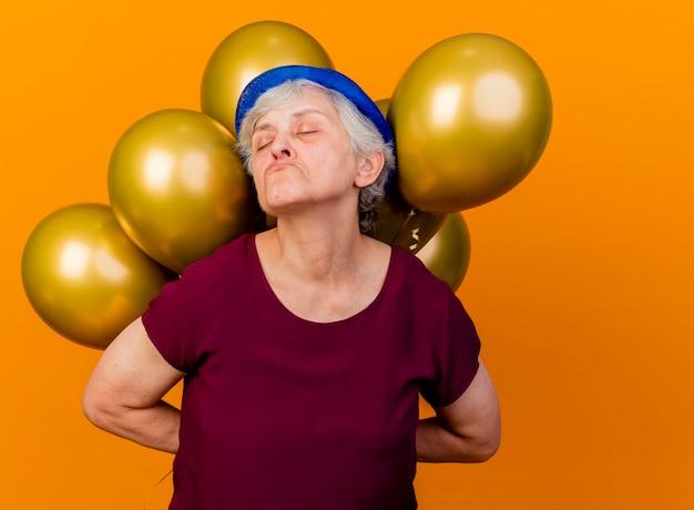 파티 모자를 쓰고 불쾌한 노인 여성은 오렌지에 닫힌 눈으로 뒤에 헬륨 풍선을 보유하고 있습니다.