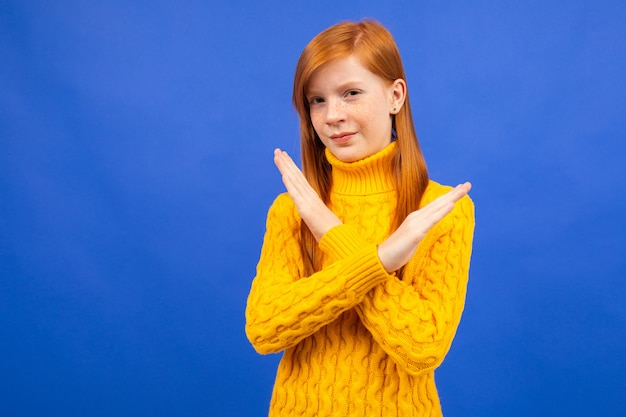 Offended european red-haired teenage girl in a yellow sweater crossed her arms in front of her on a blue