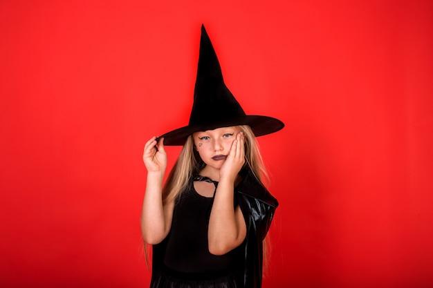 Обиженная девушка в костюме ведьмы в шляпе на красной изолированной стене с местом для текста
