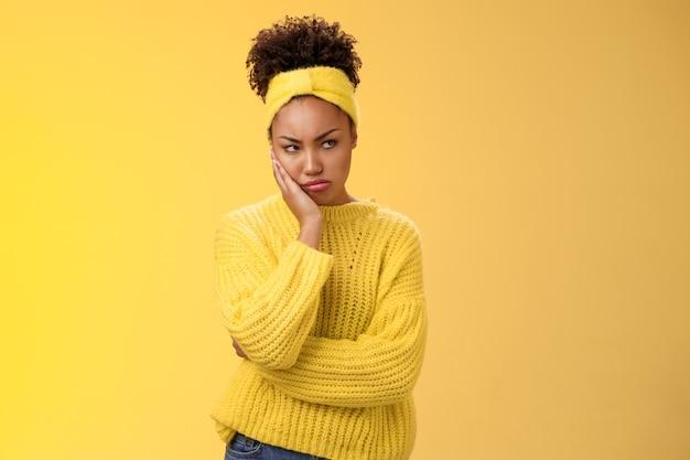 기분 나쁘게 우울한 심술을 부리는 젊은 아프리카계 미국인 여자 친구는 짜증을 내고 질투하는 표정을 짓고 짜증스럽게 찡그린 표정을 짓고 모욕적인 내키지 않는 말을 하고 노란 배경에 서 있는 누군가 마른 손 머리.