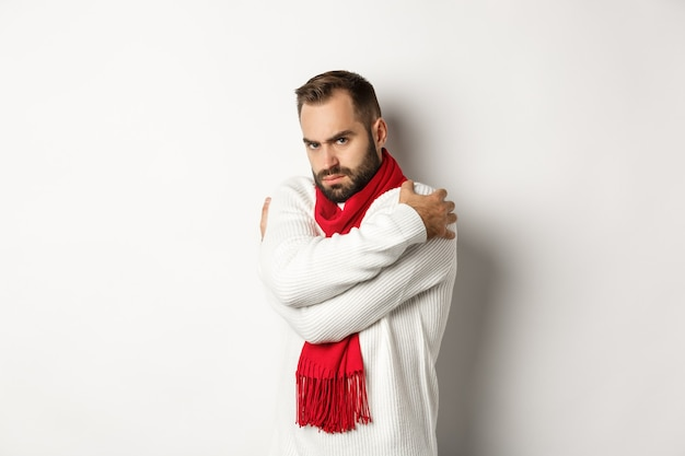 Offended guy embracing himself and looking displeased at camera, sulking while standing over white background