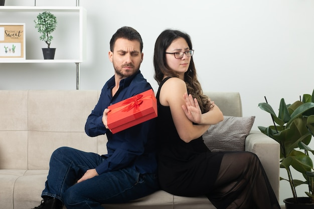 Offended handsome man giving gift box to unpleased pretty young woman in optical glasses sitting on couch in living room on march international women's day