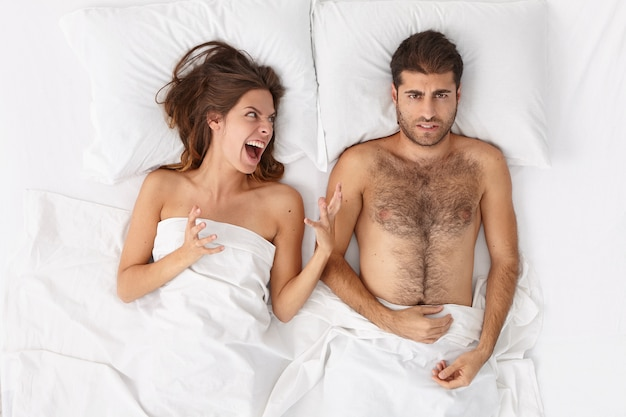 불쾌한 짜증을내는 분노한 여성은 남편과 다투고, 화를 내며 남자에게 소리를 지르며, 관계 문제가 있으며, 이별 또는 이혼을 고려하고, 침대에 머물며, 무언가에 대해 비난합니다.