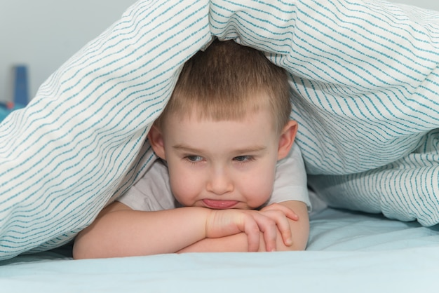 Offended little boy lays under the blanket and looks down