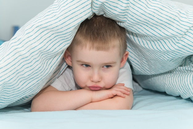 Offended little boy lays under the blanket and looks right