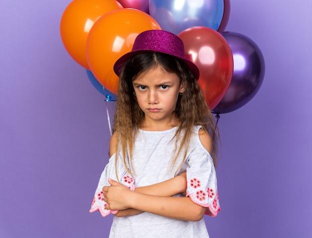 복사 공간 보라색 벽에 고립 된 헬륨 풍선 앞에서 교차 팔으로 서 보라색 파티 모자와 불쾌 어린 백인 소녀