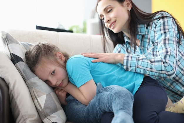 Offended little girl turned away from her mother on couch