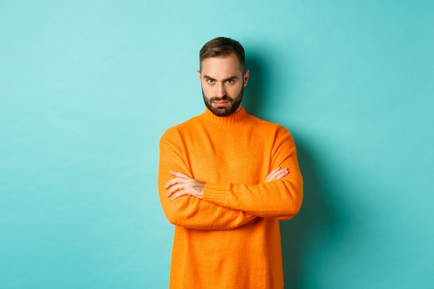 Offended man looking angry at you, cross arms on chest and stare mad, standing in orange sweater against turquoise wall.