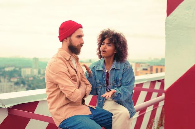 불쾌한 남자. 그의 감정적 인 여자 친구가 그에게 이야기하는 동안 심각한 젊은 남자가 인상을 찌푸리고 팔에 앉아 넘어