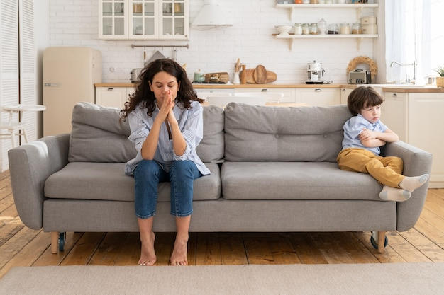Offended mom and son sit on couch in living room avoid talking