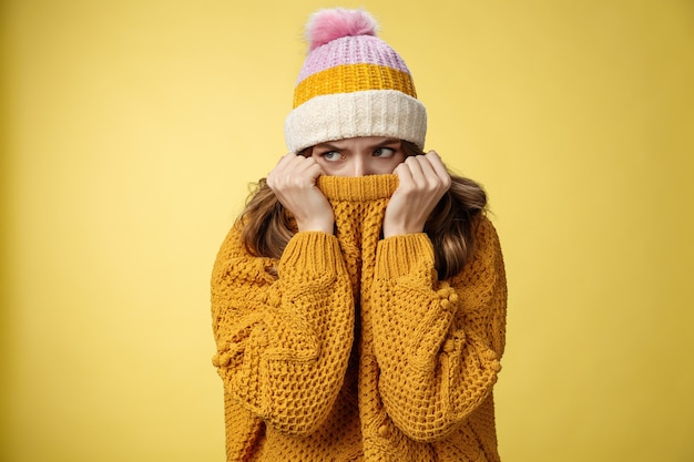 Offended sad whining cute tender young girl hiding face pull sweater nose peek look aside insulted c...
