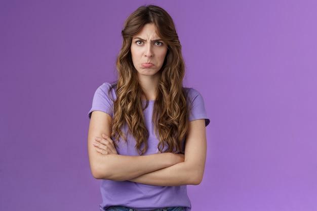 気分を害した愚かな臆病なかわいい女の子は、ふくれっ面の唇をしかめっ面して眉をひそめているクロスハンズブロックポーズ侮辱された表情不機嫌そうなカメラは演技子供っぽい不平不満不公平なゲーム紫の背景に同意しません