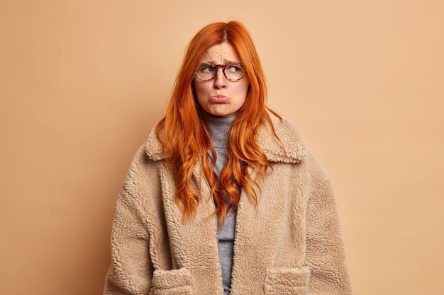 Offended sullen european woman with red hair purses lower lip and looks unhappily aside dressed in brown winter coat wants to cry from desperate emotions.