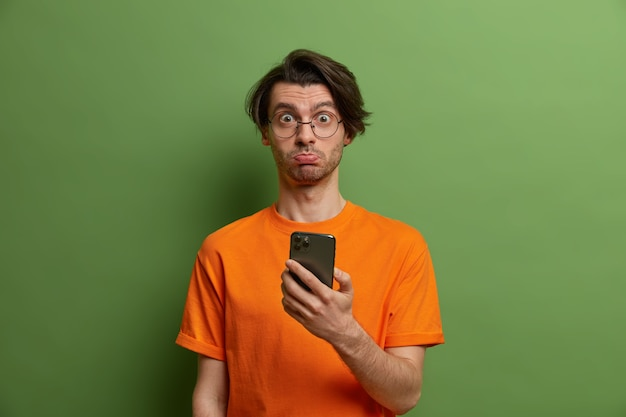 トレンディな髪型で気分を害した驚きの男は、オンラインで注文できないので不幸な顔をしており、緑の壁に隔離されたオレンジ色のtシャツを着たモダンなスマートフォンを持っています。技術コンセプト