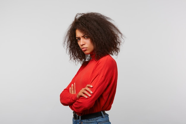 Offended upset woman with afro hairstyle in a red longsleeve standing sideways with hands crossed on a white wall