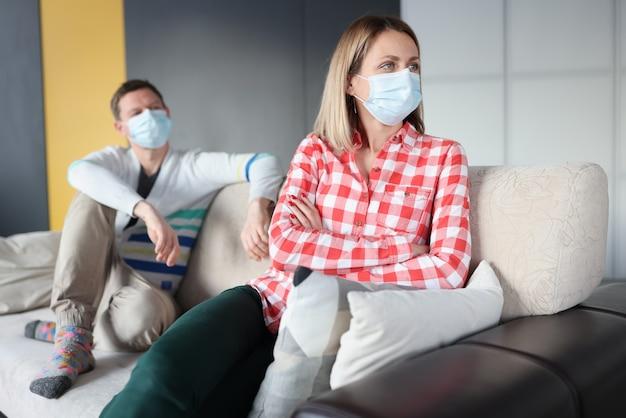気分を害した女性と男性は、保護マスクを着用してソファに座っています。検疫コンセプト後の離婚の増加
