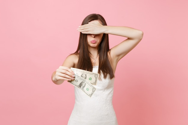 Offended woman in white dress covering eyes with palm holding one dollar bills