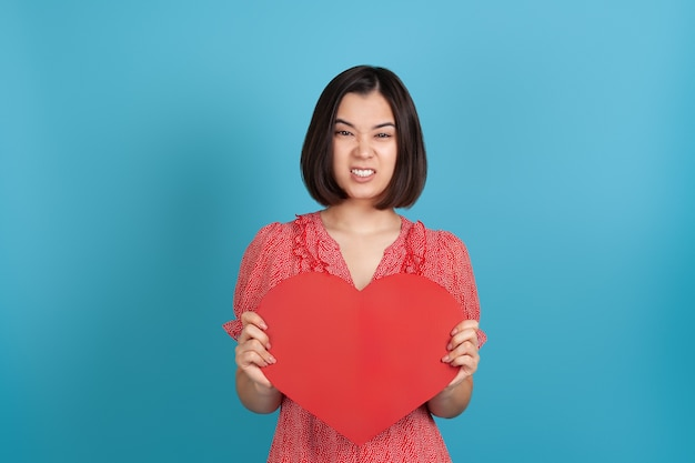 Offended young asian woman in a red dress holding a large red paper heart and baring her teeth