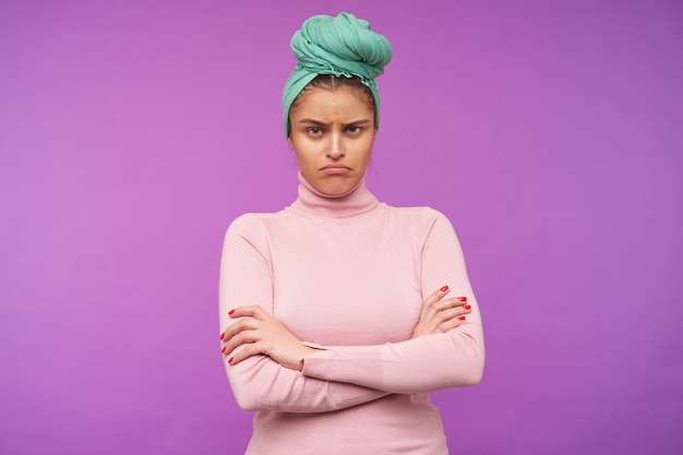 Обиженная молодая шатенка с естественным макияжем, сложив руки на груди, грустно глядя вперед, позирует над фиолетовой стеной в элегантной одежде