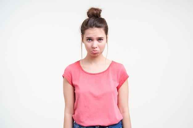 Offesa giovane donna dai capelli castani con trucco naturale imbronciato le labbra mentre guarda tristemente la fotocamera, tenendo le mani lungo il corpo mentre posa su sfondo bianco
