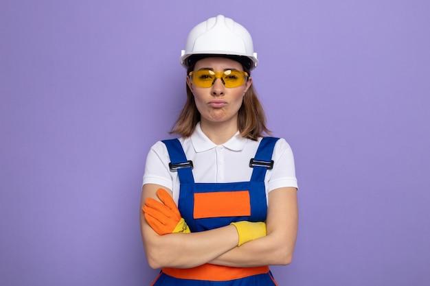 紫色の壁の上に立って腕を組んで唇をすぼめる安全黄色の眼鏡をかけているゴム手袋の建設制服と安全ヘルメットの気分を害した若いビルダーの女性