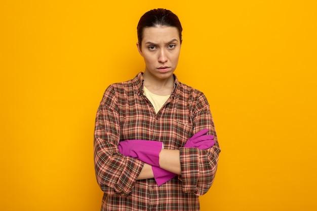オレンジ色の壁の上に立って腕を組んで眉をひそめている顔とゴム手袋でカジュアルな服を着て気分を害した若い掃除婦