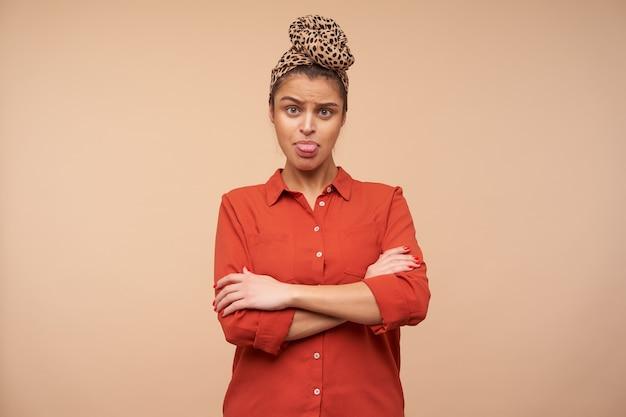 Offesa giovane donna dai capelli castani che mostra tristemente la sua lingua e piega le mani sul petto mentre si trovava sul muro beige in abiti casual