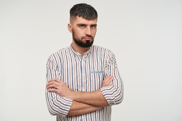 Offended young pretty brunette bearded man with short haircut crossing his hands on chest and keeping lips folded while looking sadly , posing over white wall