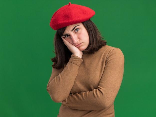 ベレー帽の帽子をかぶった気分を害した若いかなり白人の女の子は、コピースペースで緑の壁に隔離された手に頭を置きます